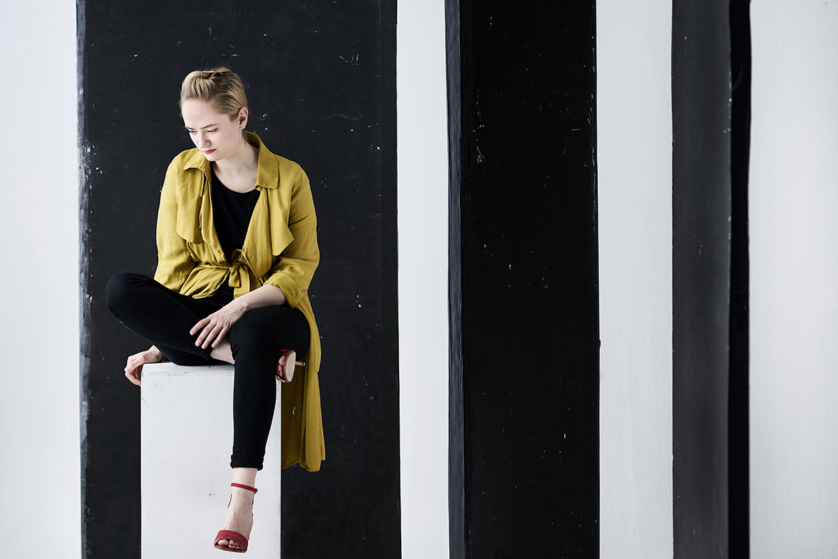 kaupo-kikkas-lady-sits-on-a-plinth-in-front-of-vertically-striped-backdrop.jpg
